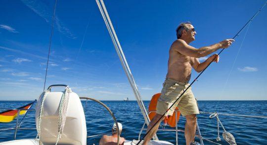 Sommer, Sonne und Fischen - Angler an Bord wirft die Angel aus