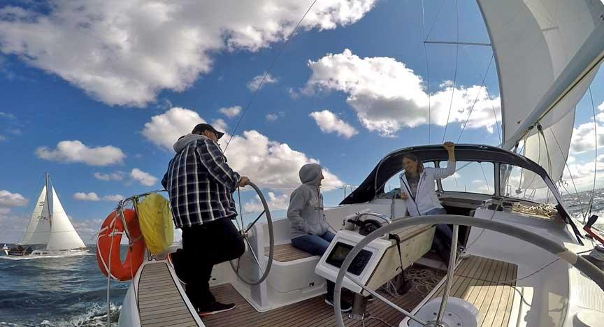 Segeln bei Sonne und Schäfchen-Wolken. Segel gesetzt und die Crew hat Spaß an Deck.