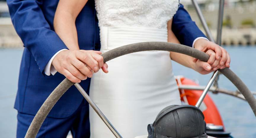 Brautpaar steht gemeinsam am Steuerrad der Segelyacht