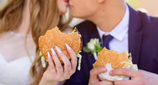 Hamburger passen selbst ins Sternelokal, warum nicht auch als Hochzeitessen. Brautpaar beim verzehr eines Burgers