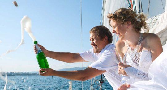 Brautpaar sitzt auf dem sonnigen Vordeck der Segelyacht und öffnet eine Sektflasche