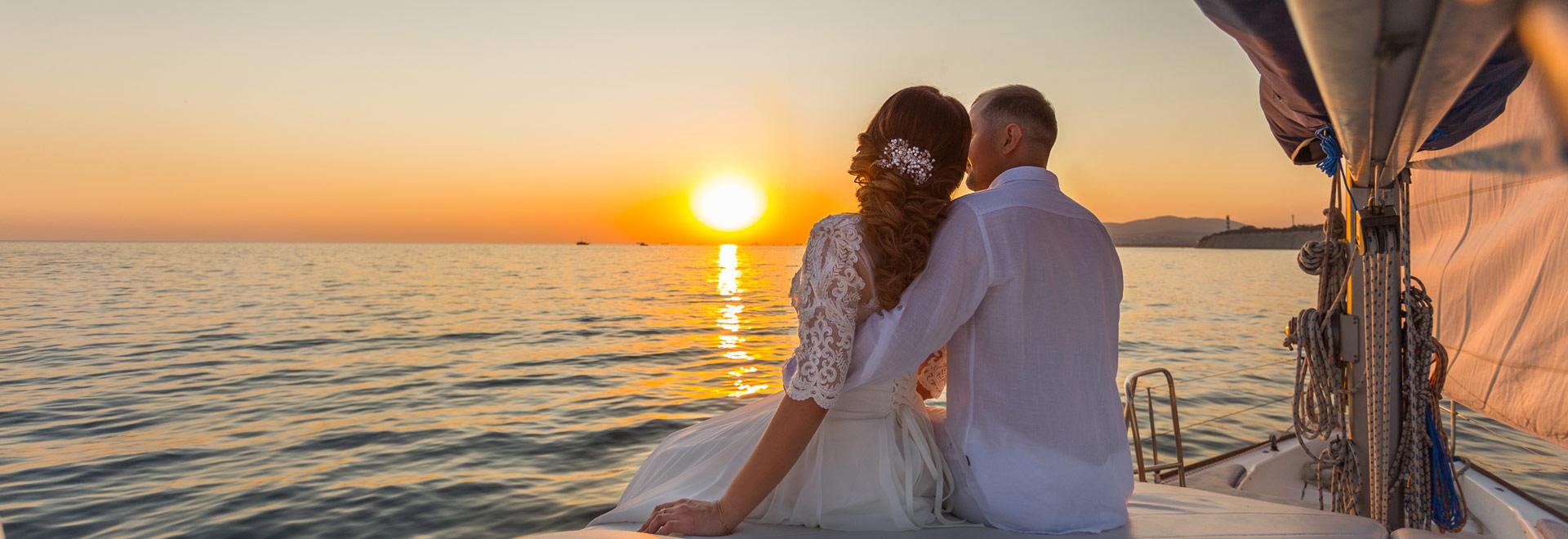 Brautpaar sitzt auf Vordeck der Segelyacht und beobachtet den Sonnenuntergang